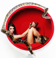 woman in red chair holdung python