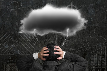 Depressed businessman with dark cloud rain lightning over his he
