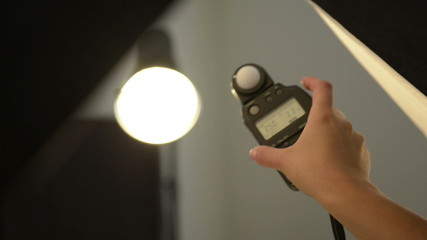 Person in photography studio using light meter to read flash