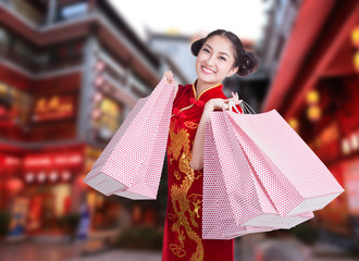 happy Chinese woman dress traditional cheongsam at street shoppi