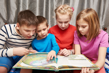Children sitting and reading geography book