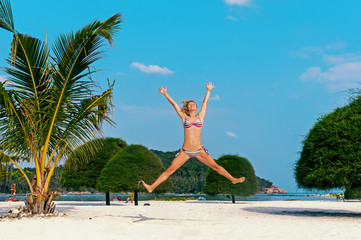 Happy woman jumping at the beach against blue sky and palm