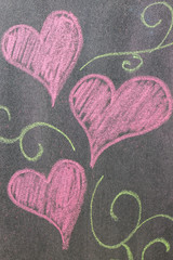 Hand drawn hearts shape on chalkboard background.