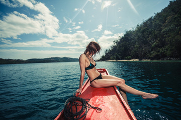 Sexy young woman on boat in the tropics
