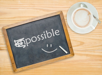 Change impossible to possible on chalkboard with coffee cup