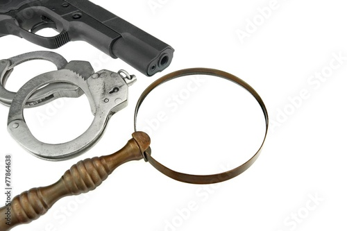 Gun, Handcuffs and Magnifying Glass Isolated on White Background