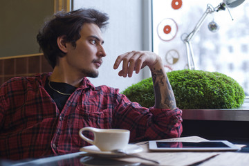 Young arabian man in cafe: flannel