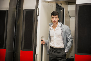 Handsome young man on train, standing in open door threshold