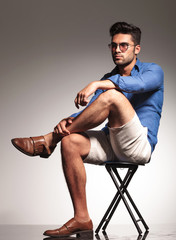 Smart casual young man sitting on a stool