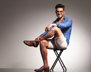 casual young fashion man sitting with his legs crossed