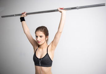 Attractive sports woman lifting barbell over gray background