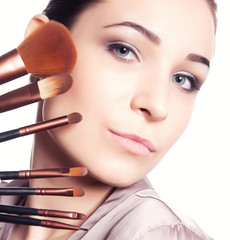 Young beautiful girl holding a set of makeup brushes.