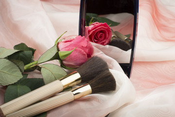 Cosmetic brushes,  a mirror and a rose