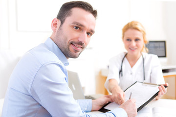 Patient signing the document of a young attractive doctor