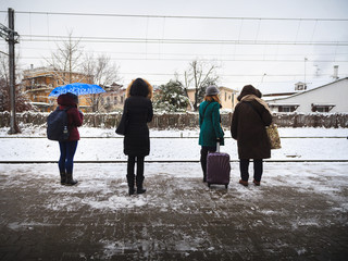 Four different women waiting for the train