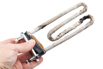Damaged heating element of the washing machine in a hand.
