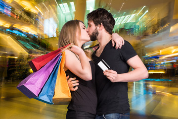 Happy kissing couple with shopping bags