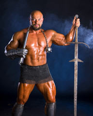 Handsome muscular ancient warrior with a sword