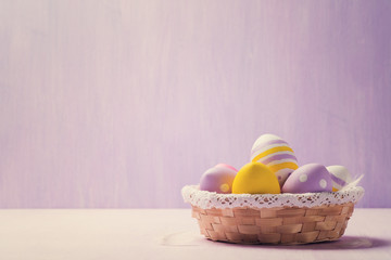 Easter eggs in a wicker basket. Space for text