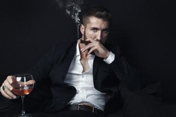 Attraktiver Mann mit Bart raucht Zigarre und trinkt Whiskey