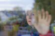 Frau hinter einer Fensterscheibe
