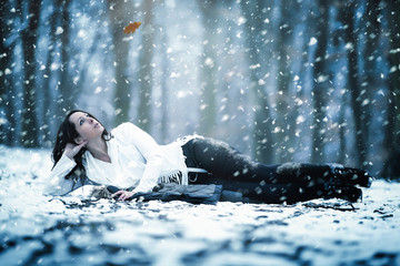 Attraktive Frau liegt im winterlichen Park