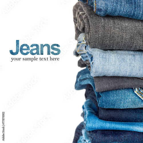 Stack of blue and black jeans as a background - 77870002