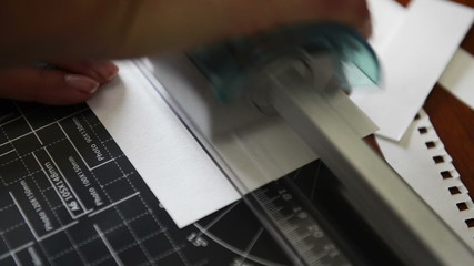 Person cutting paper on a guillotine to trim off paper edges