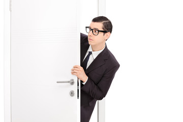 Curious young businessman looking through a door