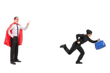 Full length portrait of a superhero chasing a burglar