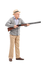 Full length portrait of an angry senior holding a rifle