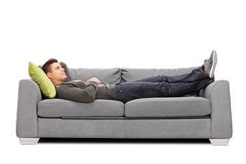 Pensive young guy laying on a sofa