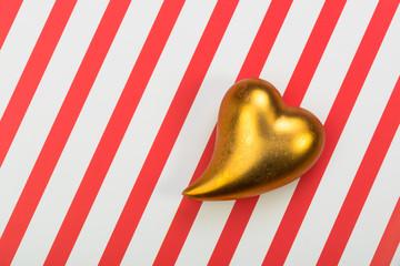 Goldenes Herz auf gestreifem Untergrund