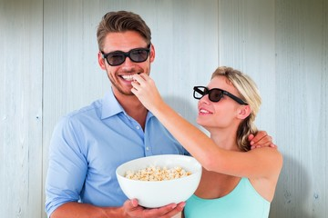 Happy young couple wearing 3d glasses eating popcorn