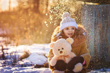 a little girl with a bear in winter