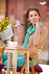 beautiful young girl drinking coffee in a old town cafe - outdoo