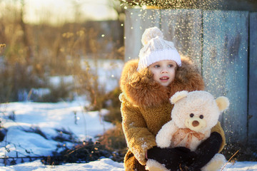 a little girl with a toy in winter