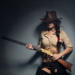girl cowboy with a gun on a gray background