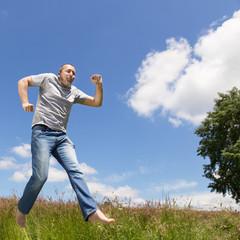 Mann springt vor blauem Himmel