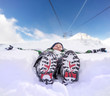 Boy lying in deep snow on the mountain hill