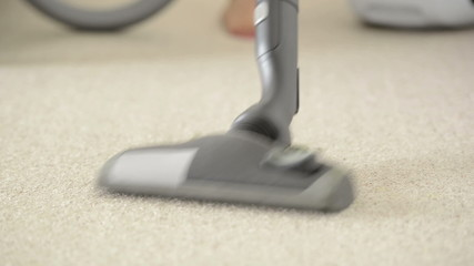 Woman using vacuum cleaner to vacuum carpet in shallow focus