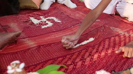 hindu brahmin conducting indian wedding ceremony making swastika