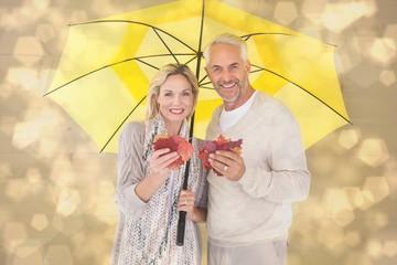 Smiling couple showing autumn leaves under umbrella