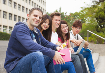 Happy  young group of students sitting on the stair