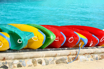 Canoes on a beach, blue water background