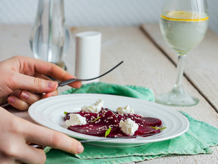 eating beet salad with goat cheese, garlic and sesame, hands