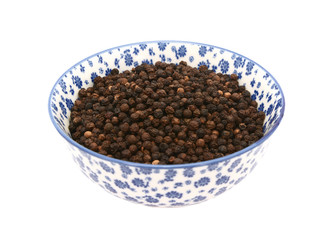 Black peppercorns in a blue and white china bowl