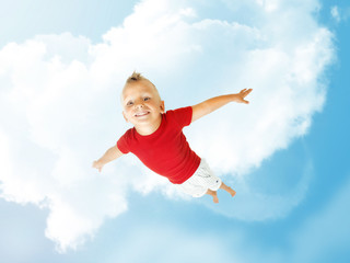 Little boy flying up into the blu sky