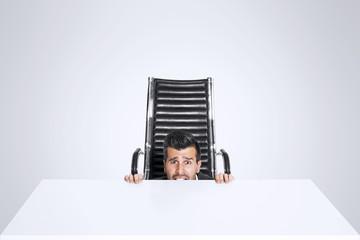 Scared business man hide himself under the office desk