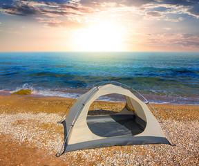 white touristic tent on a sea coast at the sunset